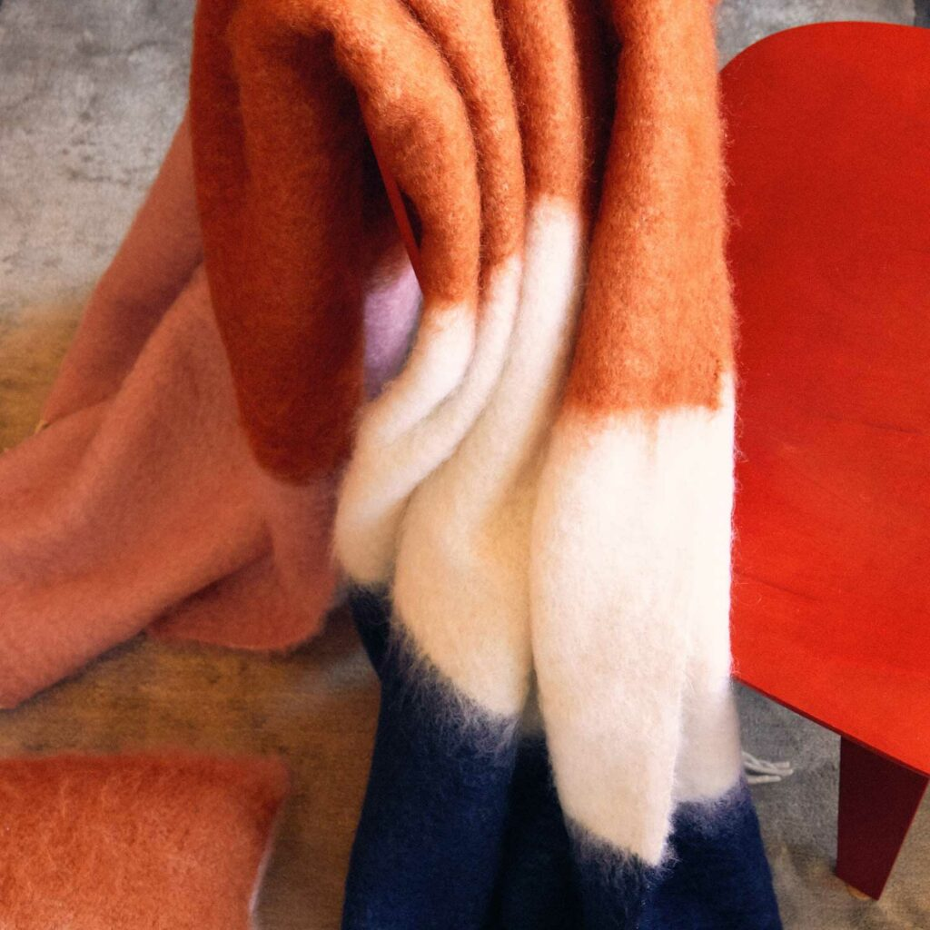 Pink, orange, white and navy mohair blanket resting on a chair