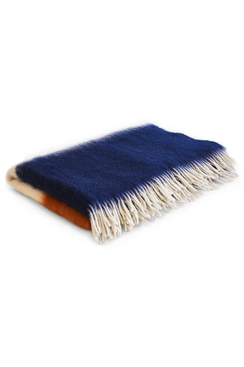 Pink, orange, white and navy mohair blanket resting on white background