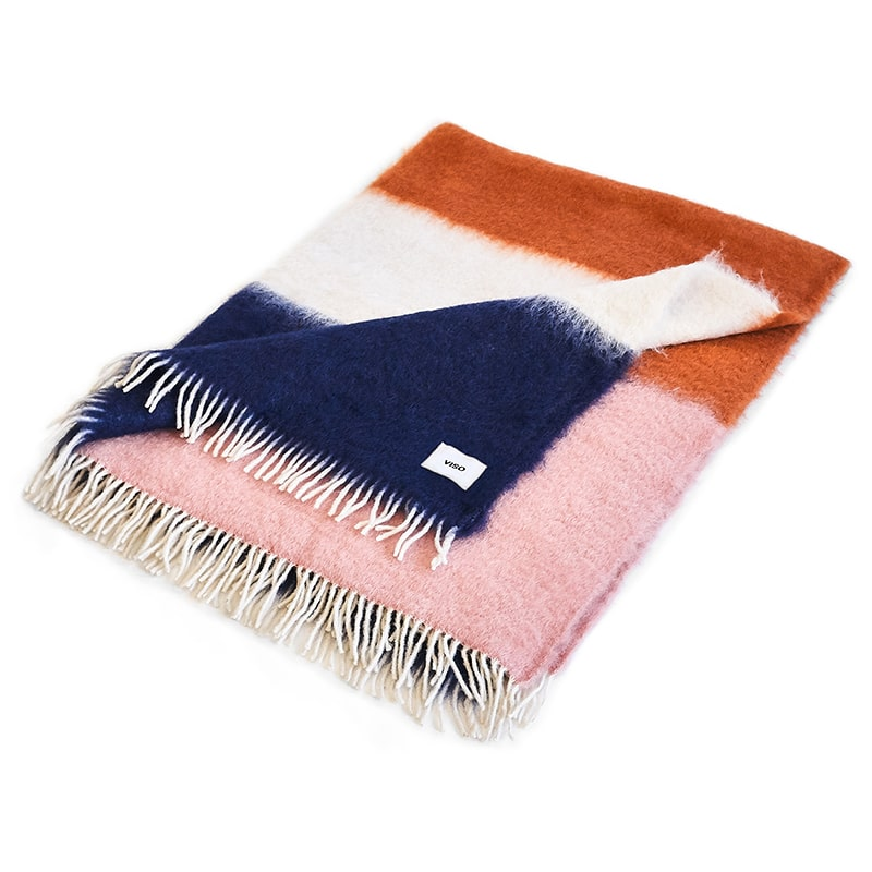 White, orange and navy mohair blanket resting on white background