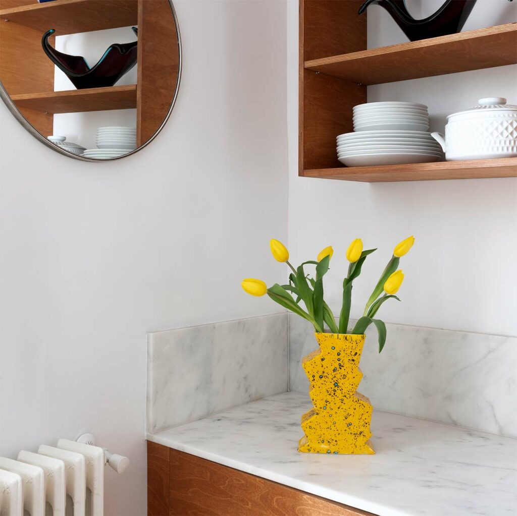 ceramic yellow vase on a marble kitchen and more decoration.